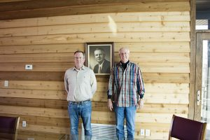 Robbie and Rob Erlbacher, with portrait of founder Robert Erlbacher.