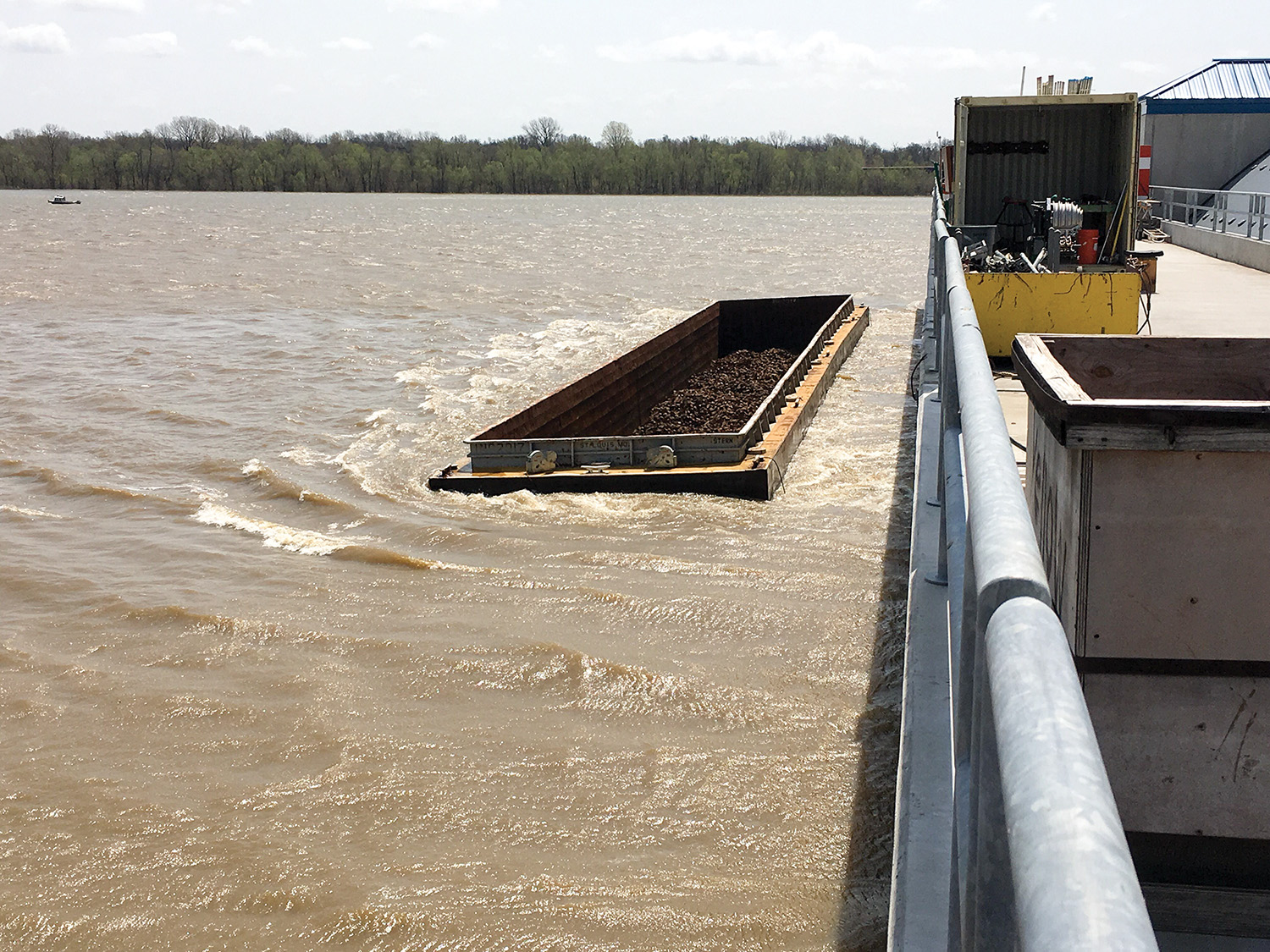A barge lodged adjacent to the Olmsted Locks and Dam is one of six that broke loose from a tow.