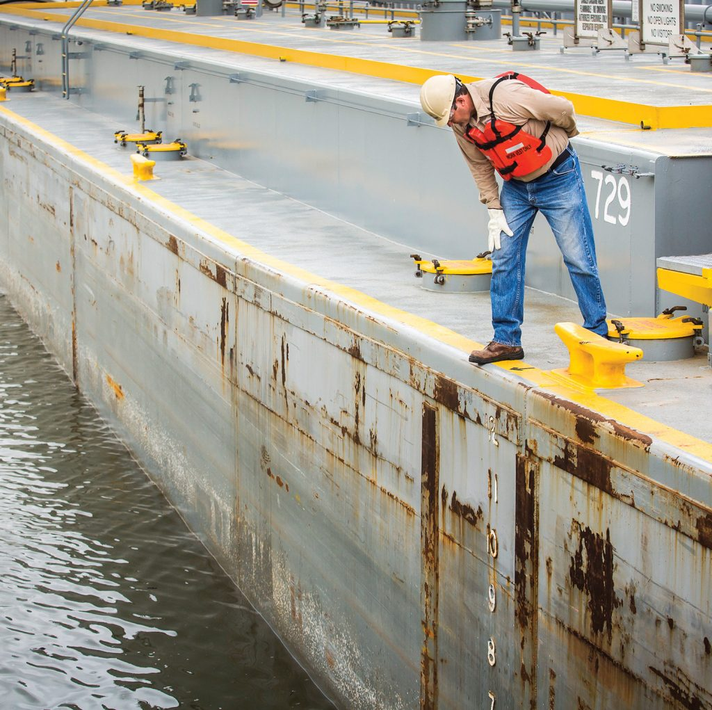 PSC Tankerman Paul Fox monitors drafts while loading a barge.(Photo courtesy of Petroleum Service Corporation)
