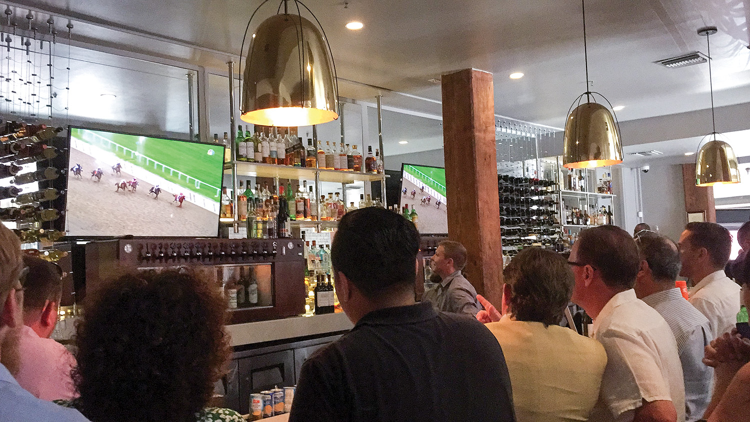 Turn Services friends and employees watch the Belmont Stakes at NOSH in New Orleans, waiting to see if Justify will win the race and the Triple Crown. (Photo by Jen McCormack)