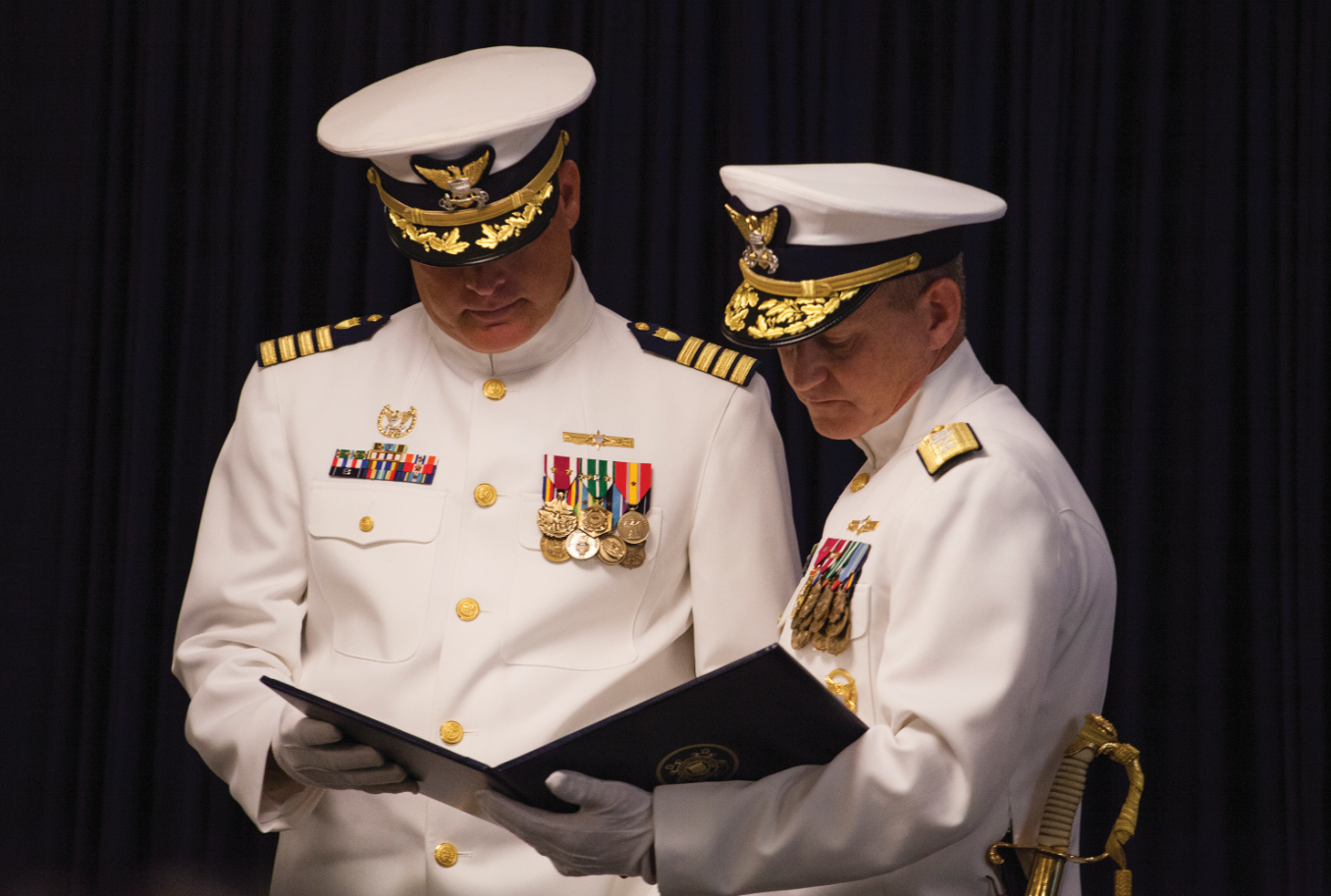 Rear Adm. Paul Thomas (right), commander of the U.S. Coast Guard's Eighth District, presents a meritorious service medal to Capt. Wayne Arguin, Sector New Orleans' outgoing commander, for his leadership at the sector, which included the 2016 response to historic rains that flooded much of the Baton Rouge and Denham Springs areas.