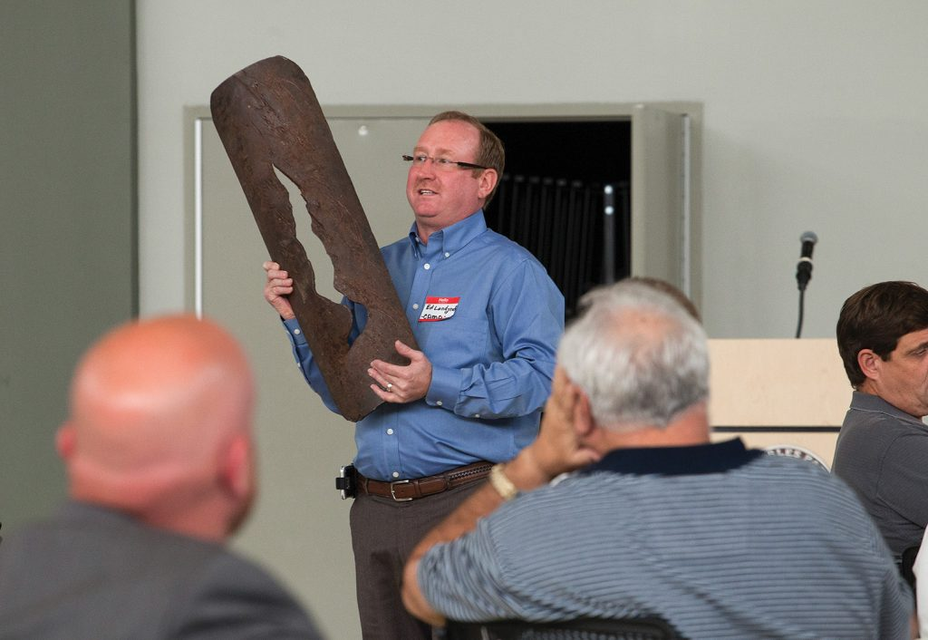 Ed Landgraf, chairman of CAMO, holding a portion of a pipeline that had seen a vessel impact. (Photo by Frank McCormack)