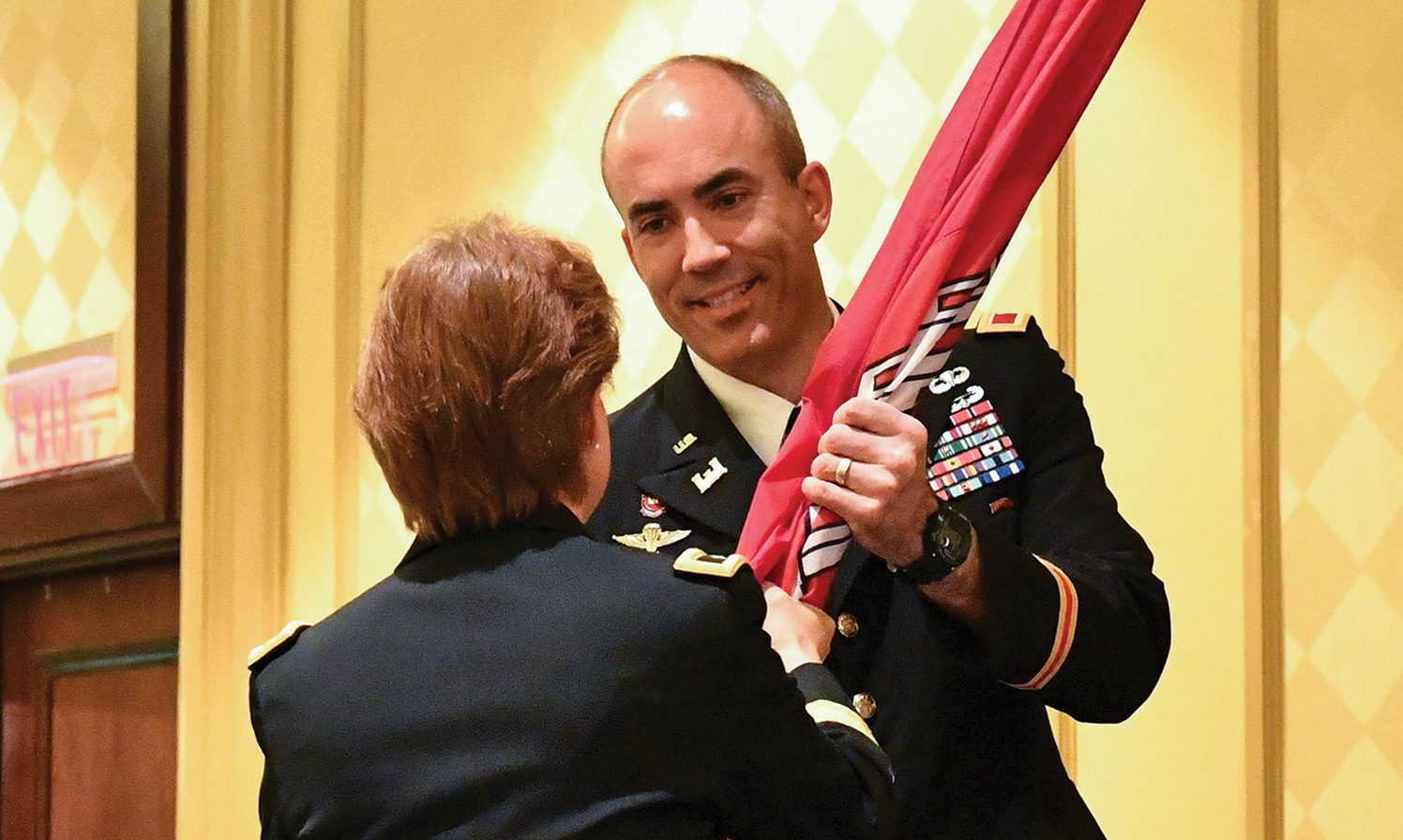Col. Sebastien Joly receives the U.S. Army Corps of Engineers flag from Brig. Gen. Diana Holland during the Mobile Engineer District change-of-command ceremony. Joly became the 53rd commander of the Mobile District. (Corps of Engineers photo by Chuck Walker)
