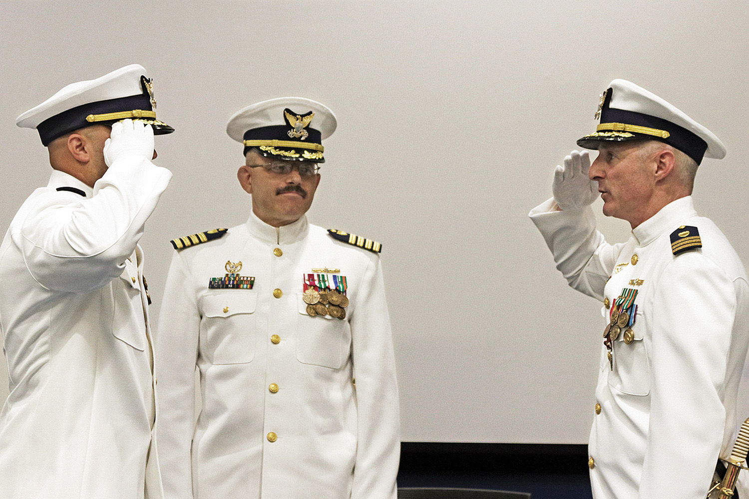 Incoming Cmdr. Luis Carmona salutes outgoing Cmdr. Mark Sawyer as Capt. Michael Zamperini looks on during July 13 change-of-command ceremony. (photo by Jeff L. Yates)