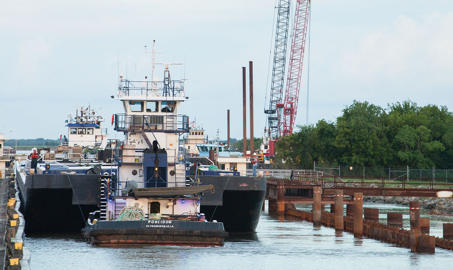 "Deloach Marine Services' mv. Poseidon assists a tow through Calcasieu Lock August 9. The ""can opener"" is on the right. (Photo by Frank McCormack)"