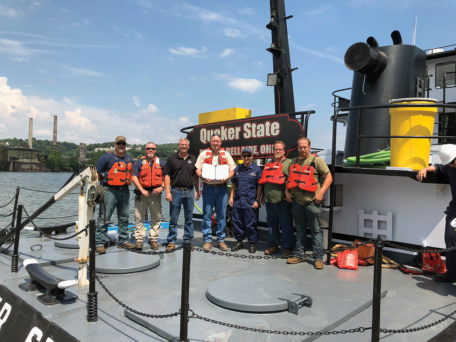 Pictured left to right are Shawn Hodgson, maintenance director; Roger Garretson, EHSS director; Ron Harrison, port captain; Robert Harrison, owner; Aaron Demo, Coast Guard Captain of the Port of Pittsburgh; Jeff Stephen, vessel captain; and Kevin Lyons, deckhand. (Photo courtesy of Bellaire Harbor Service)