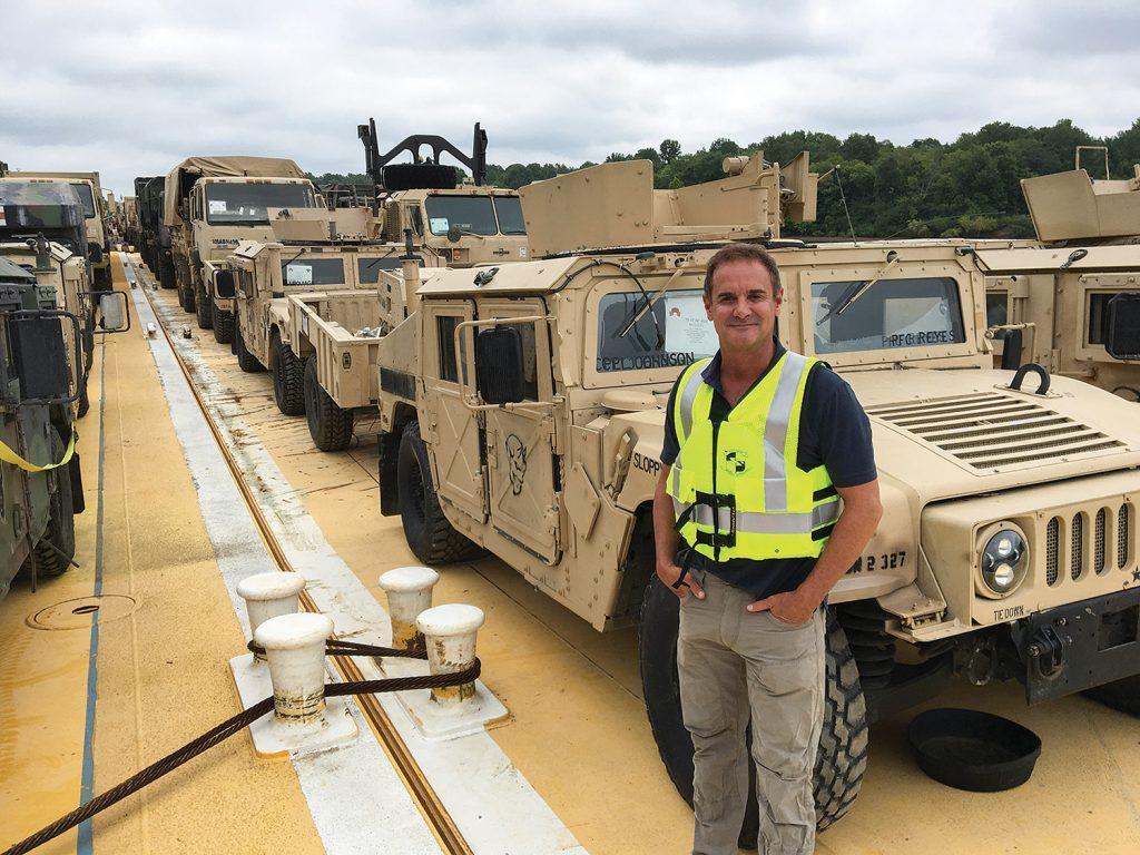 Dan Frankum, president of Glenn E. Daulton Inc., poses onboard one of 45 deck barges loaded with military equipment and vehicles. (Photo courtesy of Glenn E. Daulton Inc.)
