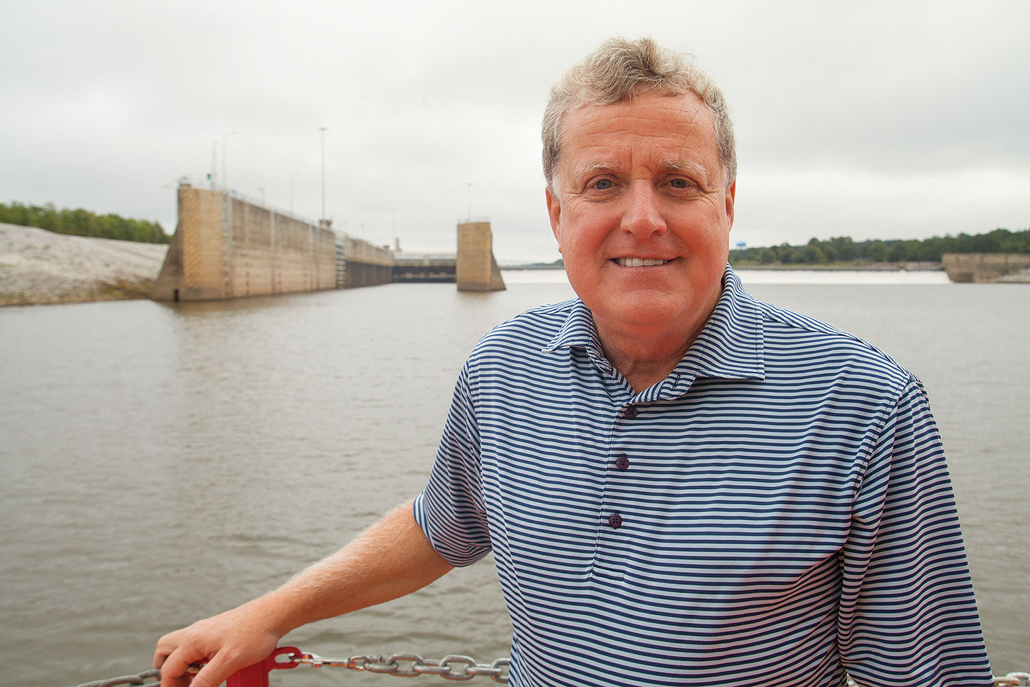 Danny Hensley, retired operations project manager for the Black Warrior-Tombigbee and Alabama-Coosa Waterways, aboard the Corps' crane barge Choctawhatchee September 28, the day of his retirement. Oliver Lock and Dam on the Black Warrior River is in the background. (Photo by Frank McCormack)