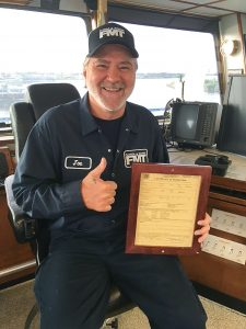 Capt. Joe Kent of the mv. Ron Hull holding the boat's COI.