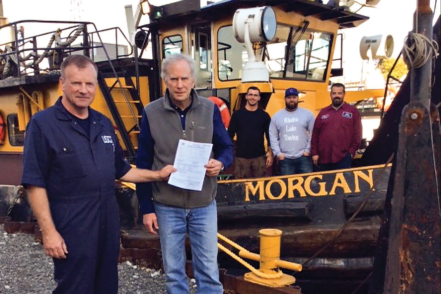 Jeff Carie, Marine Safety Unit-Chicago, presents John Kindra, president of Kindra Lake Towing LP, with its first Certificate of Inspection for the mv. Morgan as the vessel's crew looks on. Crew members include Nijaz Jahovic, deckhand; Capt. Mike Hunter; and Ken Horn, deck engineer. (Photo courtesy of Kindra Lake Towing)