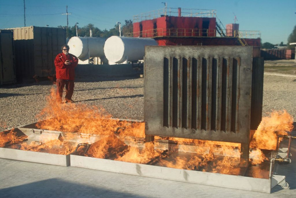 "Ricky Heyd, fire school coordinator, demonstrating remote control ignition of two of the four new ""props"" on the school's fire field."