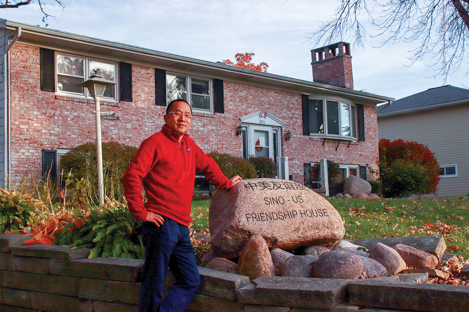 Chinese investor Glad Cheng stands in front of the former private residence where Chinese President Xi stayed in 1985. The home attracts some Chinese tourists to Muscatine and is managed by the city, but Glad pays the taxes and maintenance. (Photo by Emery Styron)