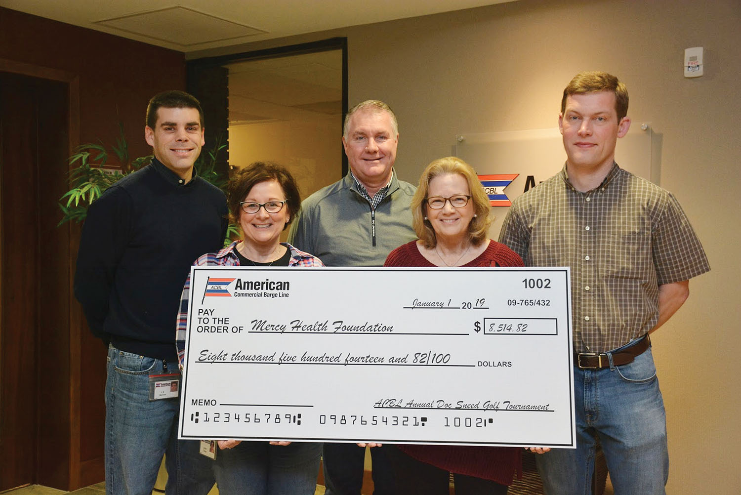 Displaying the proceeds from the 2018 tournament are J.B. Meiman, director logistics boat planning; Jenifer Tretter, administrative assistant; Rich McCarty, director of grain and fertilizer; Kathy Sneed; and Neil Collins, ACBL director of purchasing.