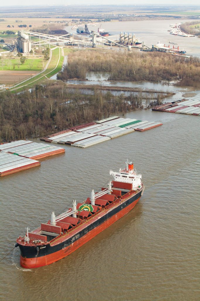 Fleets near Welcome and Convent, La., as well as both the Zen-Noh grain elevator (one of seven grain elevators within the Port of South Louisiana) and a conveyor leading from Nucor Steel's direct reduced iron plant. (Photo by Frank McCormack)