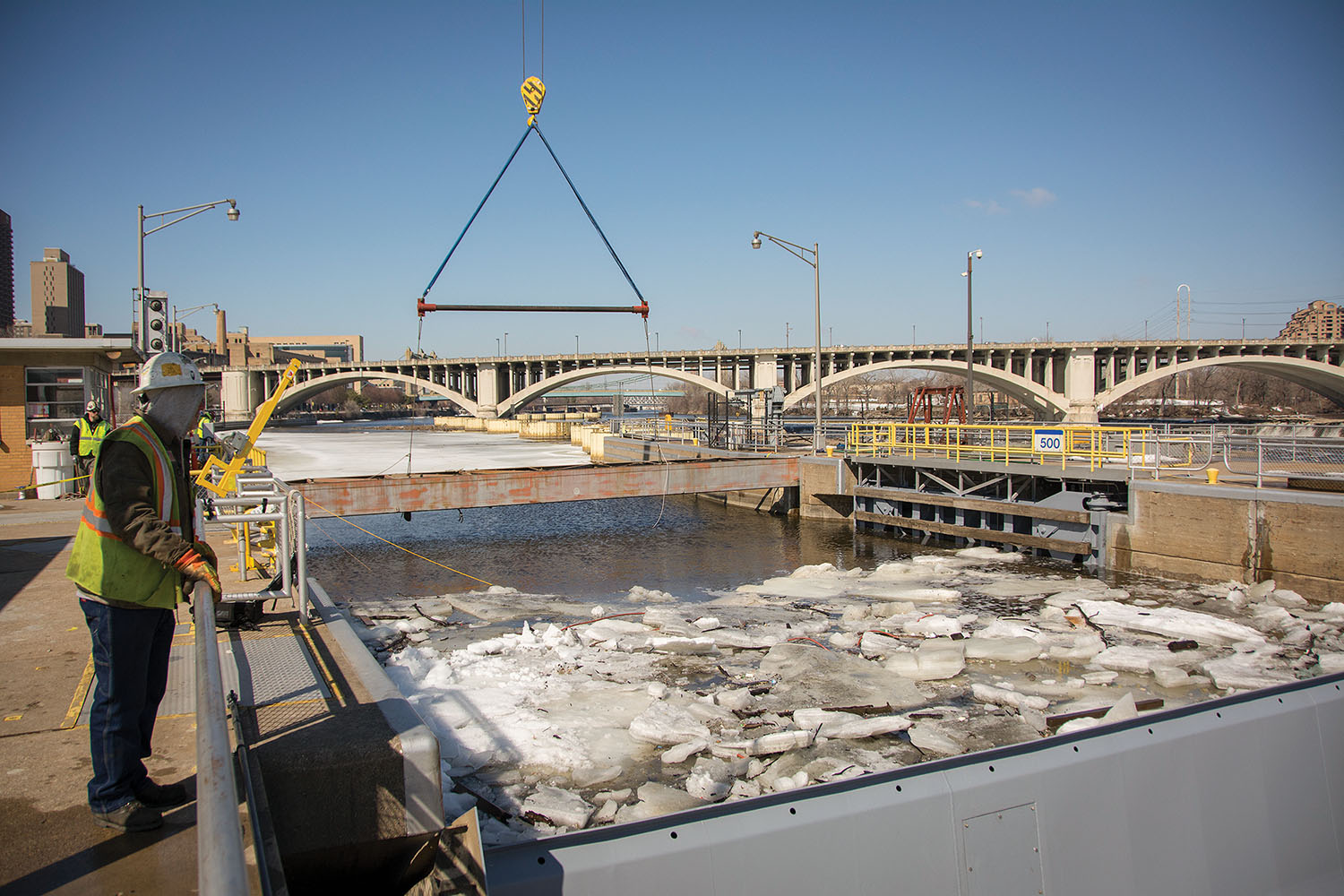A contractor crews lifts steel bulkheads on the upstream side of the St. Anthony Falls Lock on March 20, a tricky maneuver completed in advance of anticipated high flows resulting from snowpack melt in the Mississippi headwaters. (Corps of Engineers photo by Patrick Loch)