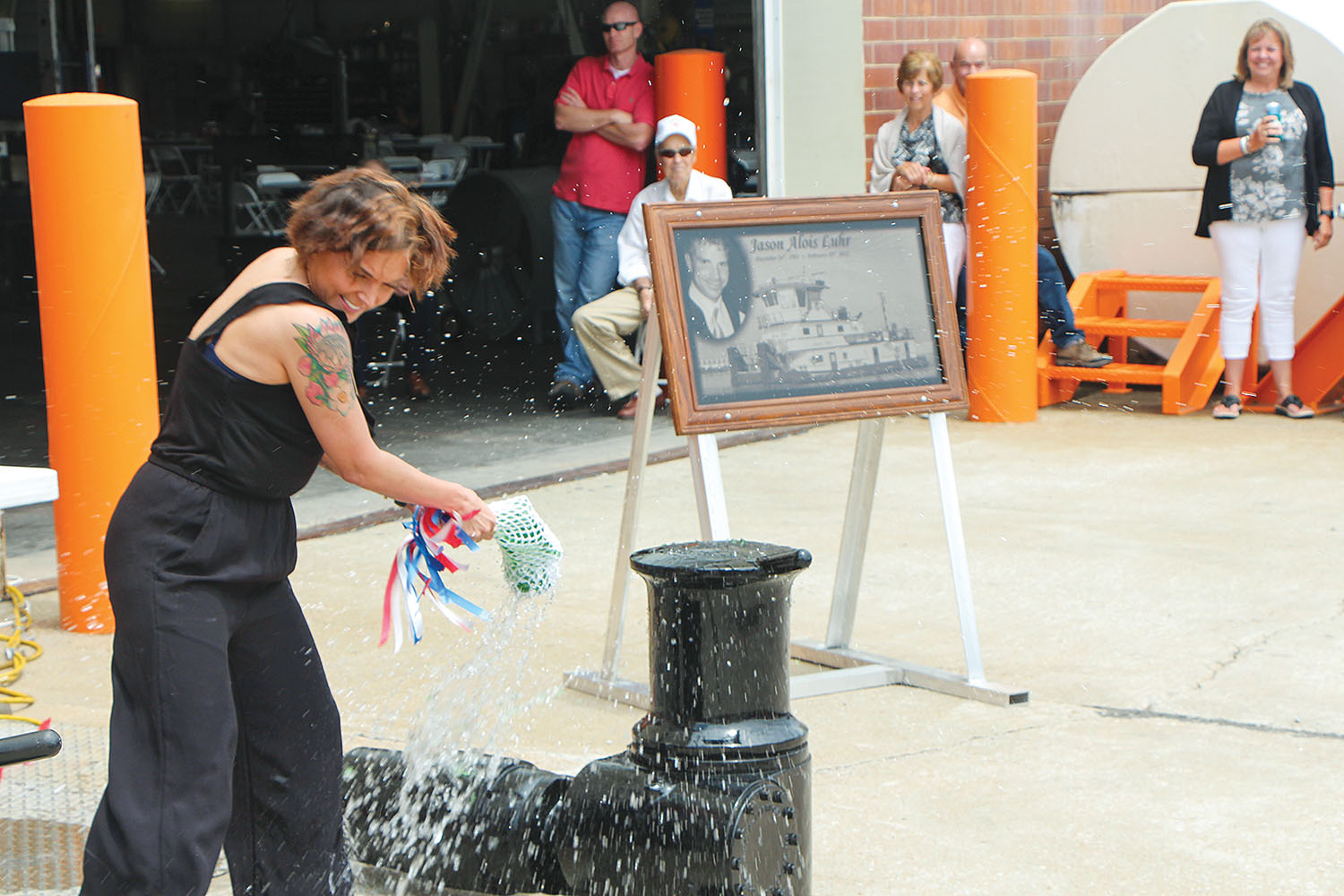 Kacie Maxwell breaks champagne bottle over mock-up of mv. Jason Luhr. (Photo by H. Nelson Spencer)
