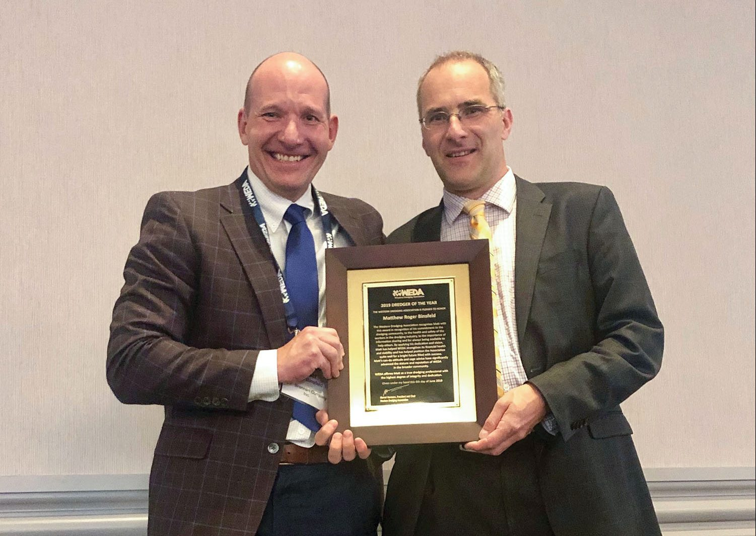 Matt Binsfeld, left, president and CEO of J.F. Brennan Company, receives the 2019 Dredger of the Year award from Marcel Hermans, president and chairman of WEDA, during the WEDA Dredging Summit and Expo.