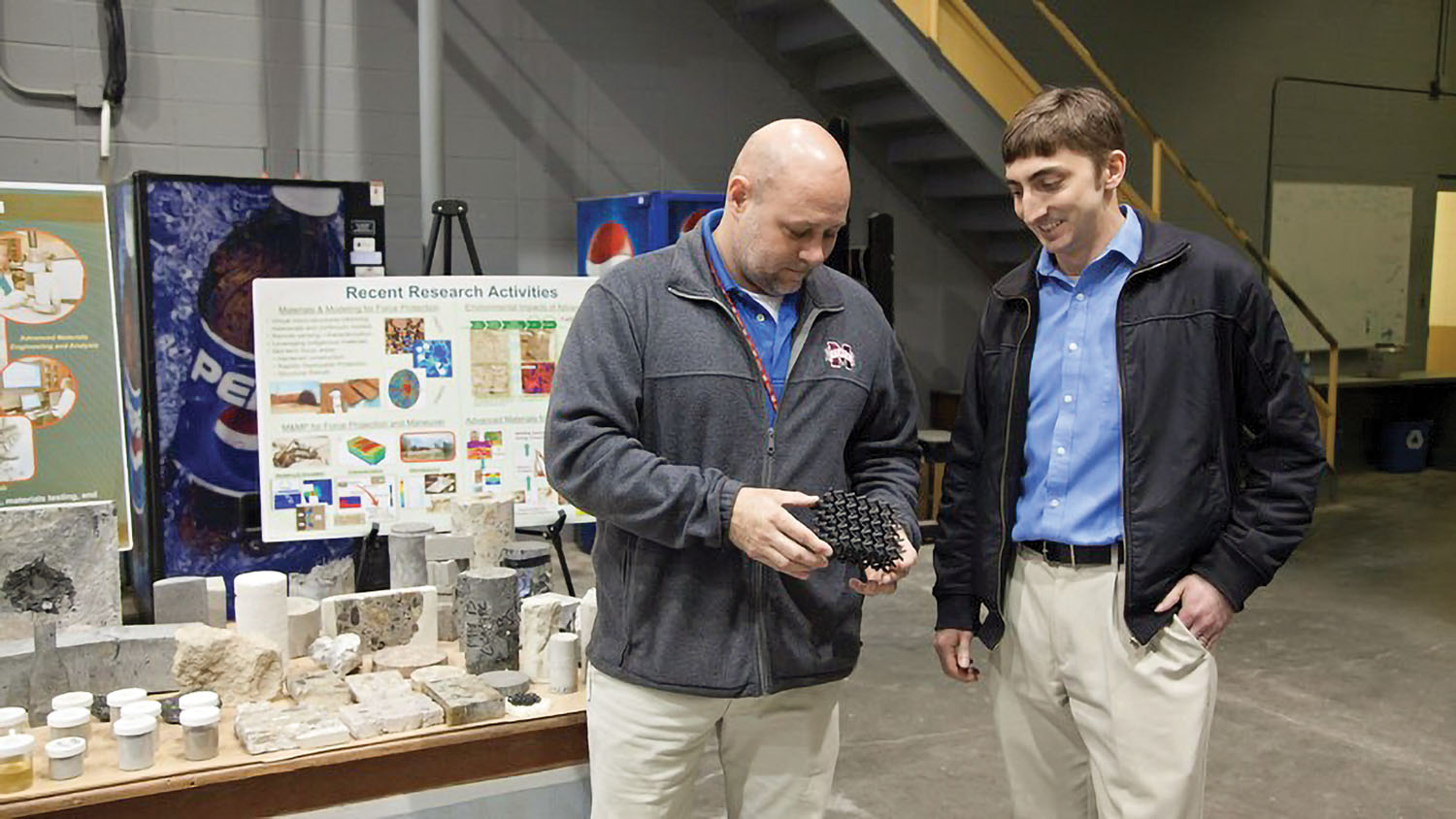 Brian Lucarelli, right, a civil engineer in the Pittsburgh Engineer District, tours the Geotechnical and Structures Laboratory at the U.S. Army Engineer Research and Development Center in Vicksburg, Miss. At left is the lab's Concrete and Material Branch Chief Christopher Moore, who is holding a sample of  polylactic acid material, which is 3-D printed into a lattice structure to enhance structural performance and energy dispersion.