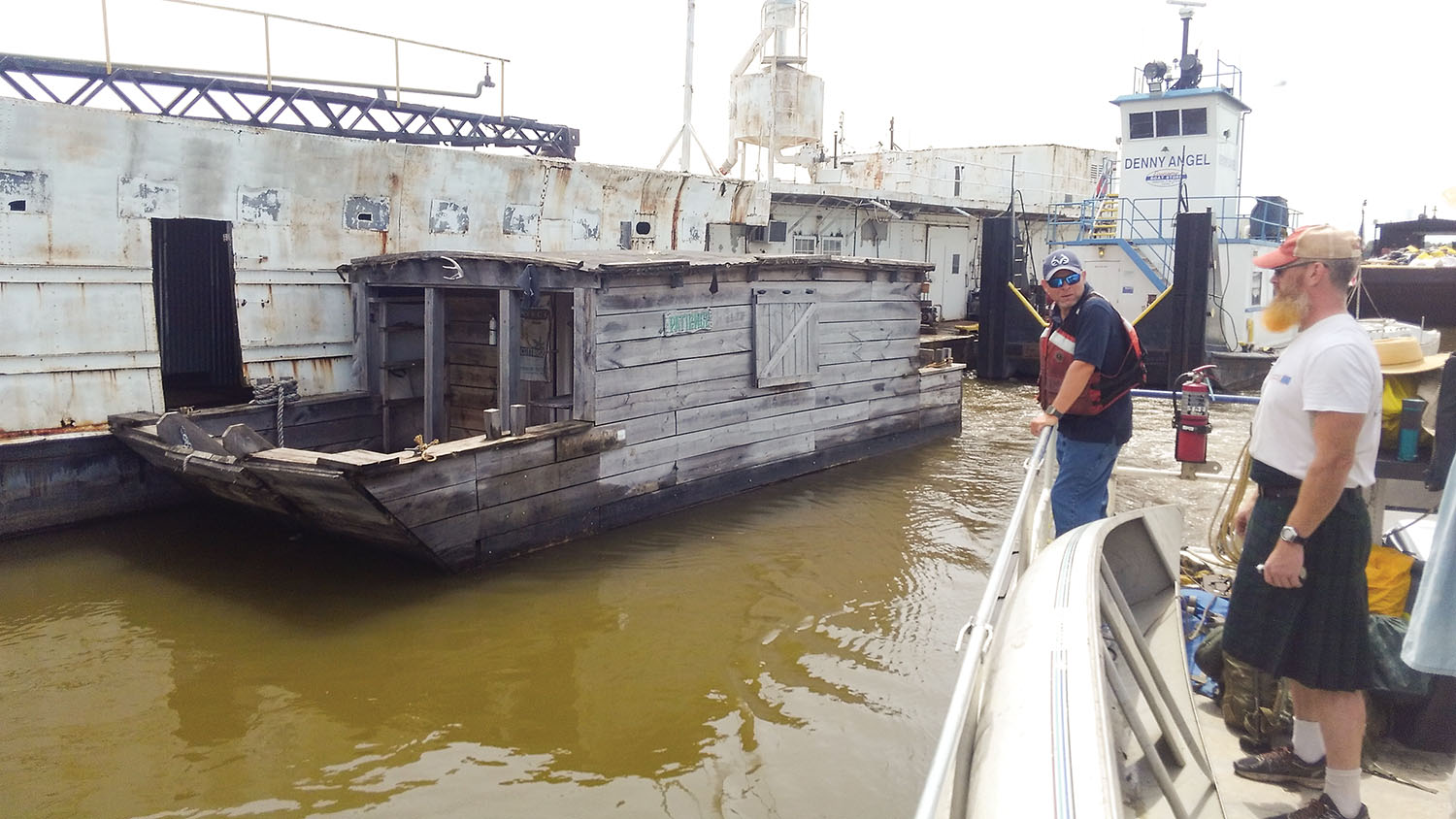The replica flatboat Patience moored at the Economy Boat docks in Wood River, Ill.; a member of boat-builder Scott Mandrell's crew looks on. (Photo courtesy of Scott Mandrell)