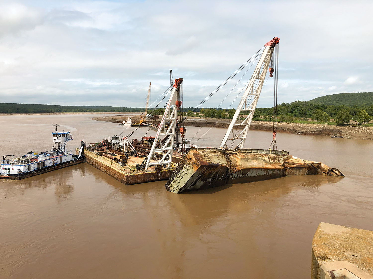 Salvaged barge is moved upstream where it will be cut up for scrap. (Photo courtesy of Tulsa Engineer District)