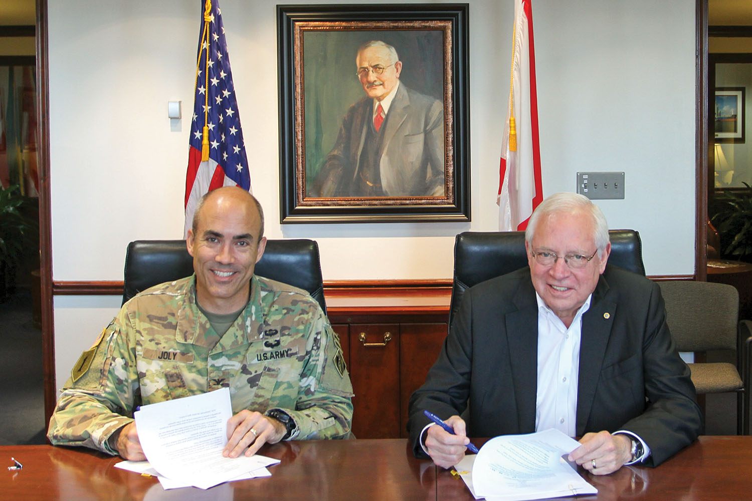 Col. Sebastien Joly and James Lyons sign PED agreement at the Alabama State Port Authority's headquarters. (Photo courtesy of Alabama State Port Authority)