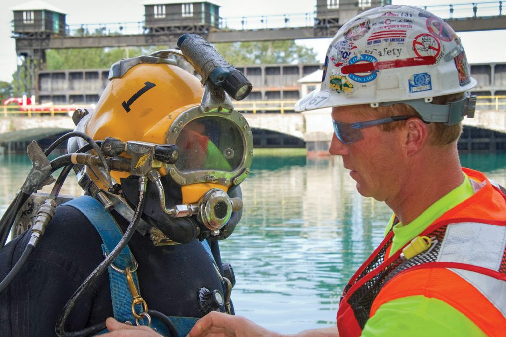 A dive tender, in hard hat, double checks the diver's equipment prior to the dive. The tender will keep his attention on the umbilicals and monitoring equipment the entire time the diver is underwater. (Photo courtesy of J.F. Brennan Inc.)