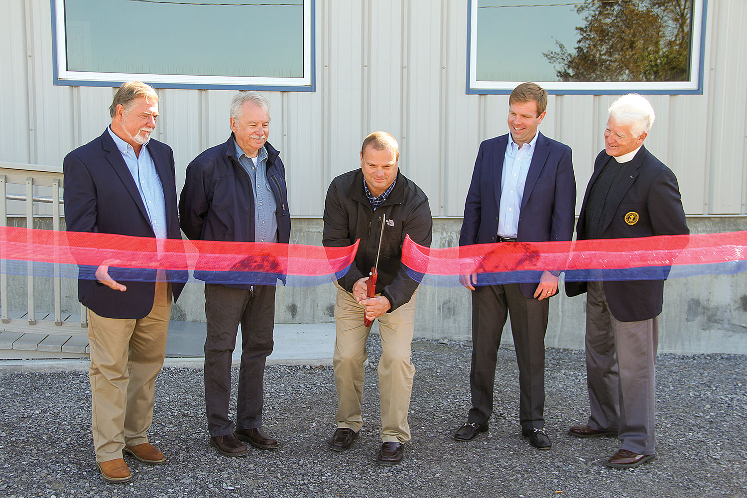 Ballard County Judge-Executive Todd Cooper cuts the ribbon to officially open Economy Boat Store as operations manager Barry Kelly (left), Wickliffe Mayor David Phillips, David Reynolds, managing director of Economy Boat Store, and Chaplain Kempton Baldridge look on.