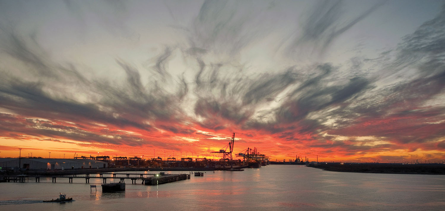 The sunset paints the sky over the Houston Ship Channel and one of Port Houston's container terminals. (Photo courtesy of Port Houston)