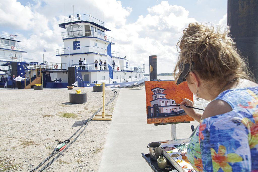Stacey Rhoades, wife of the Rev. Thomas Rhoades, adds an artistic touch to the festivities by painting the mv. Ed S. (Photo by Frank McCormack)