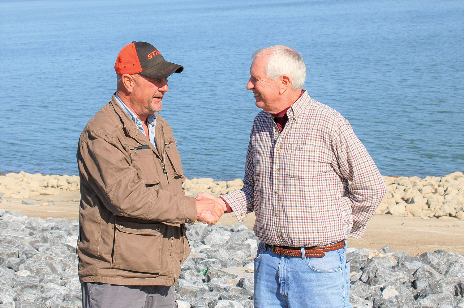 Bruce McGinnis (left) and Rob Erlbacher shake hands following the sale of floating assets belonging to Erlbacher's Missouri Dry Dock & Repair Company Inc. to McGinnis's McNational Inc. The men have been friends about 15 years and began discussing the private sale about a year ago. Missouri Dry Dock is retaining its machine shop and propeller shop. (Photo by Shelley Byrne)