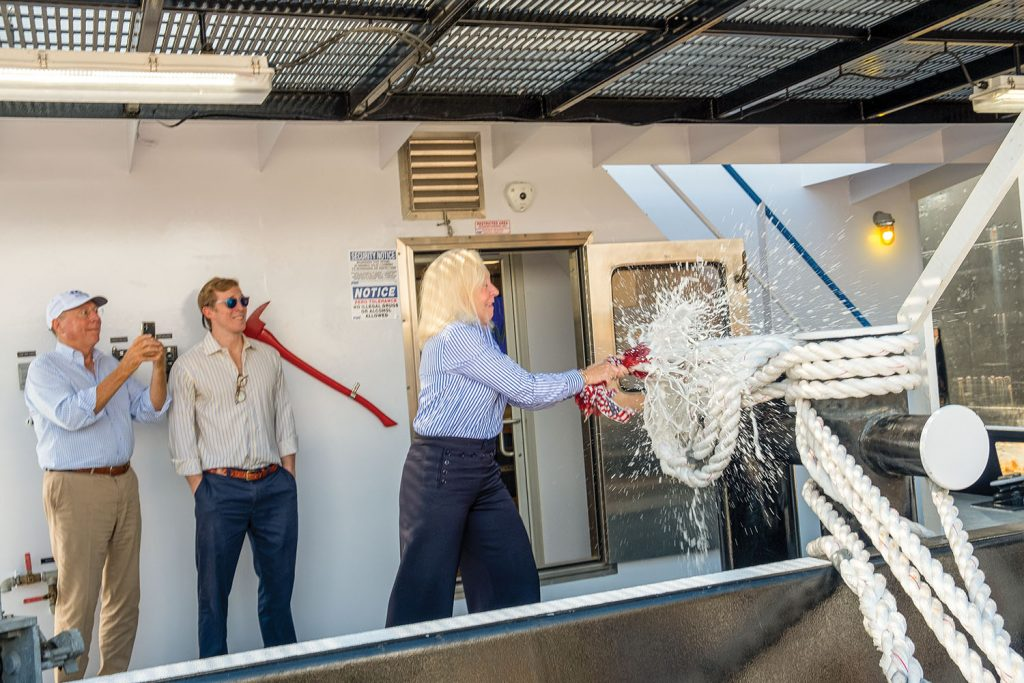 "Louise ""Ouizee"" Brooks smashes a champagne bottle to christen the mv. Ouizee. (Photo courtesy of Maritime Partners)"