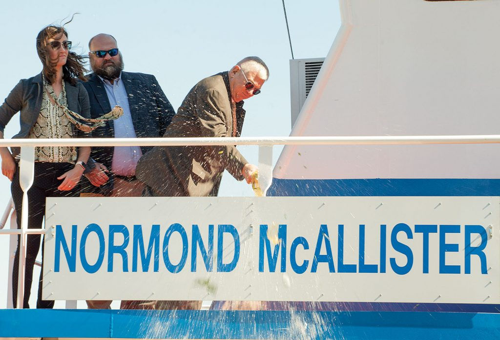 Normond McAllister christens his namesake vessel. Also pictured are Alison Phillips, recruitment manager and director of communications for Parker Towing, and Chas Haun, executive vice president. (Photo by Frank McCormack)