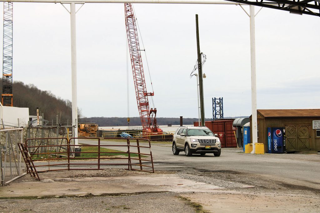 A sport utility vehicle passes by on the Eddyville Riverport's main access road. A nearly $50,000 grant will allow the road to be realigned to reduce traffic congestion. It will include removing the fence at left as well as the concrete pad remaining from a conveyor belt project as well as widening, leveling and resurfacing the road. (Photo by Shelley Byrne)