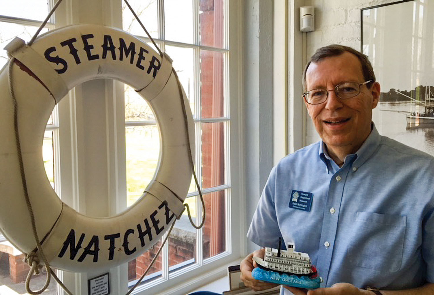 Newly retired Howard Steamboat Museum director/curator Keith Norrington poses with a model of the steamer Natchez in front of a donated ring buoy from the Natchez in 2018 at the museum. (Photo courtesy of Howard Steamboat Museum)