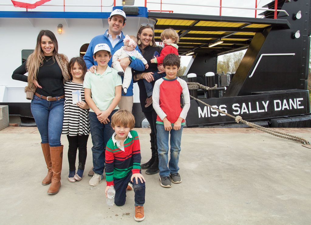 Austin and Sally Sperry stand before the mv. Miss Sally Dane December 20, following the christening ceremony for the Maritime Partners vessel. Pictured also are their children Kenison (with Austin), Henry (with Sally), Genevieve, Jack and John Austin (front middle), along with cousin Grayson (front right) and Maddy, the children's nanny. (Photo by Frank McCormack)