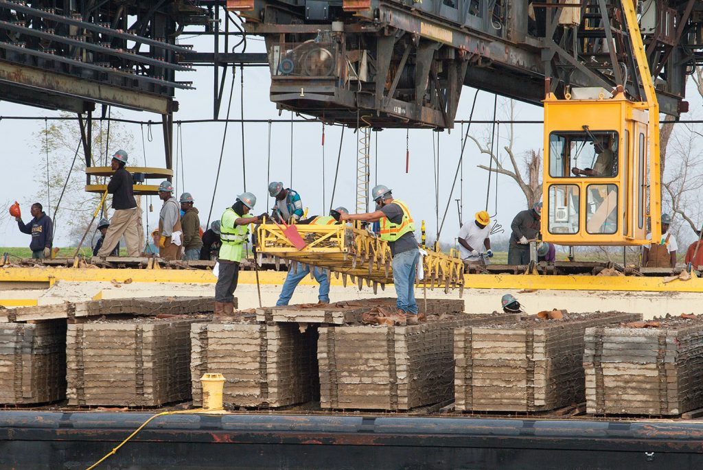 MSU crew members transfer concrete squares from a deck barge onto the mat laying barge. (Photo by Frank McCormack)