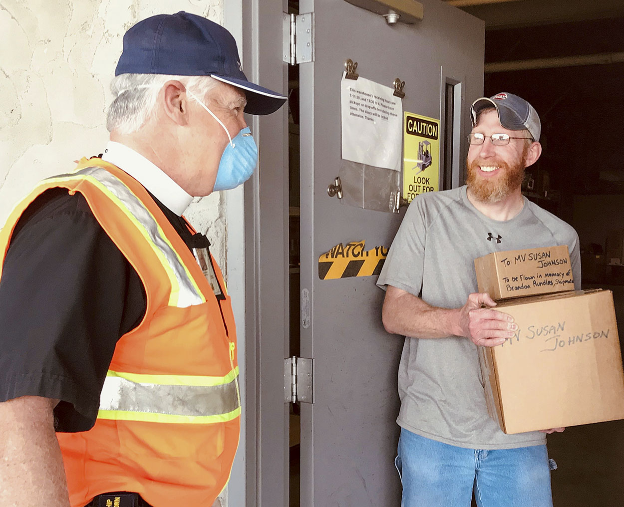 "In a pastoral response adapted to the realities of the global pandemic, Senior River Chaplain Kempton Baldridge transfers two parcels to Brandon Land, supervisor at Ingram Barge Company's warehouse in Paducah, Ky., for further delivery to an Ingram towboat crew on the Lower Mississippi River. With all vessel visits curtailed, chaplains must communicate their care and concern for crews by different means. Thus, after learning of a crewmember's death earlier in the day, Chaplain Baldridge packed up the flag of the U.S. Merchant Marine to fly in the mariner's memory and a large morale box loaded with books, DVDs, dental kits, snacks and prayer books for his shipmates, ever mindful to observe ""social distancing"" protocols. (Photo courtesy of Seamen's Church Institute)"
