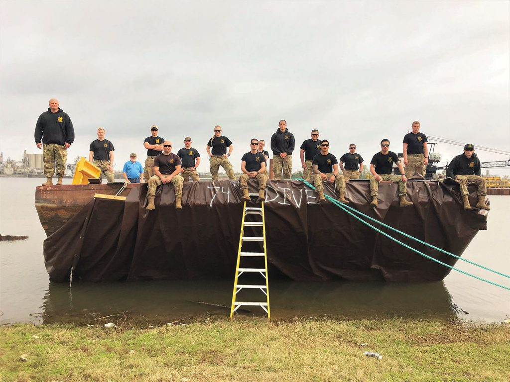 The 74th Army Dive Detachment Team sits atop the barge they successfully removed from the Ensley Engineer Yard stringout. Pictured left to right in the front row are 1st Sgt. Donald Lester, master diver; Staff Sgt. Richard Lee, dive supervisor; Staff Sgt. Trevin Currey, dive supervisor and noncommissioned officer in charge; Sgt. Alex Fanning, salvage diver, Spc. Nolan Hurrish, 2nd class diver; and Sgt. Michael Brown, salvage diver. Pictured left to right in the second row are 1st Lt. Christopher Thompson, diving officer and officer in charge; Sgt. Daniel Sivori, salvage diver; Sgt. Samantha Howleger, medic; and Pfc. James Lews, 2nd class diver. Pictured left to right in the third row are Sgt. Joshua Staats, salvage diver and Staff Sgt. David Corrales, salvage diver. Pictured left to right in the last row are Marine Facilities and Equipment Specialist Chad Chrisco, Pvt. Brady Harris, mechanic; and Spc. Pierce Castro, salvage diver. (Photo courtesy of the Memphis Engineer District)