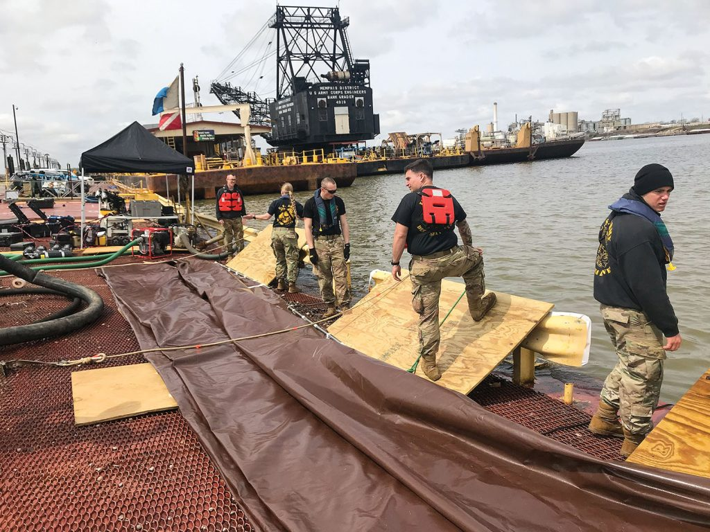 Members of the 74th Army Dive Detachment Team prepare to deploy one of the three tarps used to stabilize and remove the barge from the stringout. (Photo courtesy of the Memphis Engineer District)