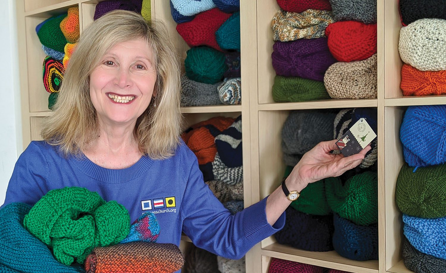 Joanne Bartosik, manager of Seamen's Church Institute's Christmas at Sea/Christmas on the River program, shows off some of the many knitted items SCI collects to give out as Christmas gifts to mariners. (Photo courtesy of Seamen's Church Institute)