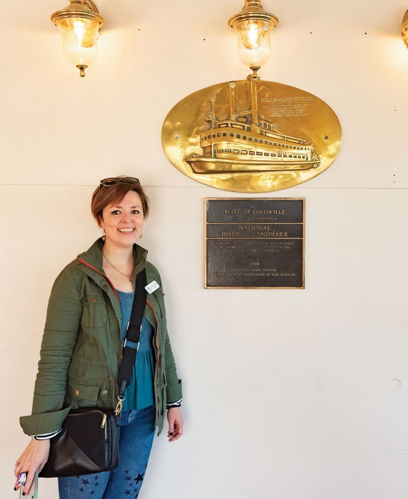 Belle of Louisville Riverboats CEO Krista Snider stands next to the Belle's national historic landmark plaque. Snider started with the organization in August 2019, tasked with making it more sustainable and relevant to new audiences. (Photo by Kristen Warning)