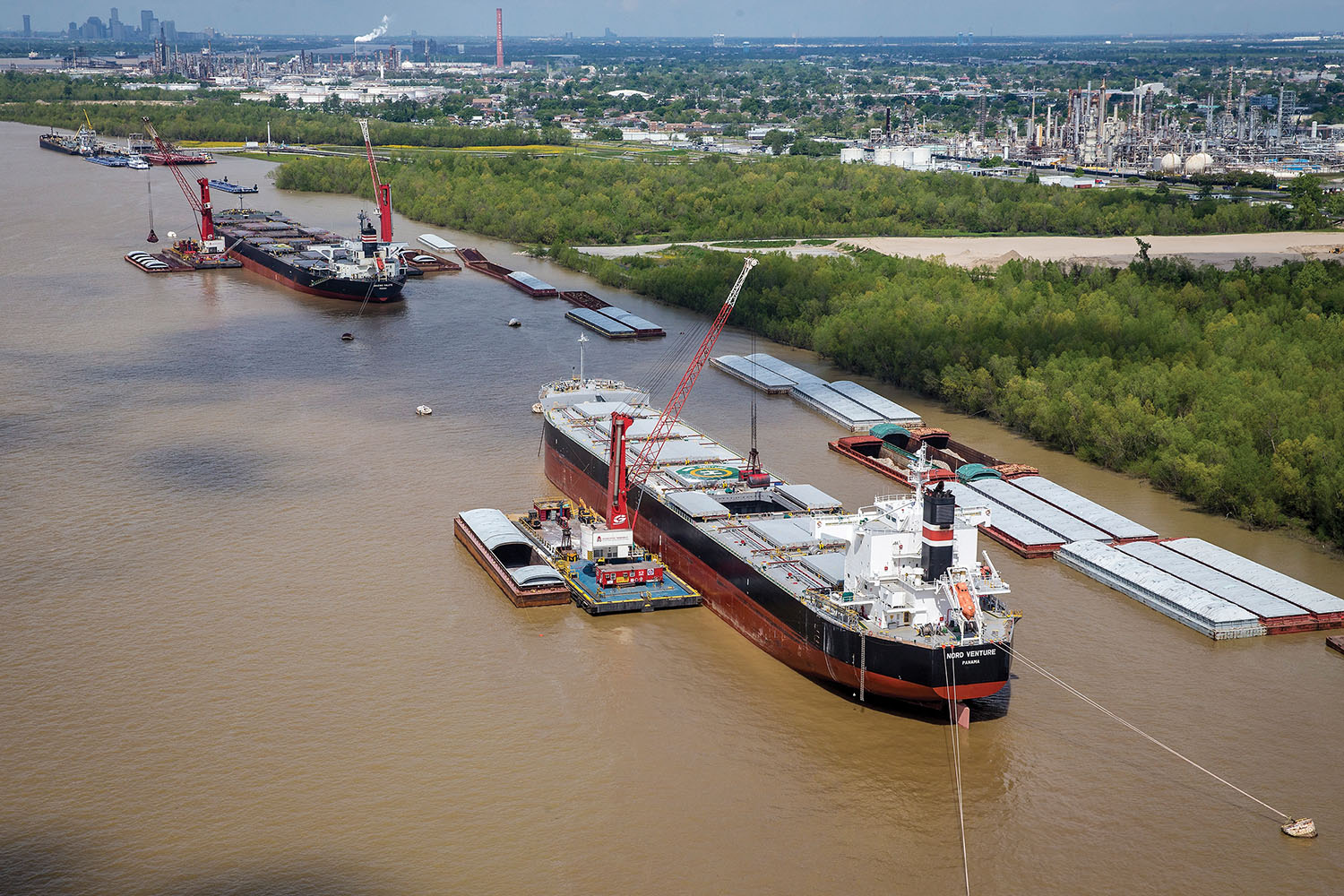 A pair of Associated Terminal's floating Gottwald cranes transfer cargo between barge and ship near Violet, La., on the Mississippi River within the Port of St. Bernard. (Photo courtesy of Associated Terminals)