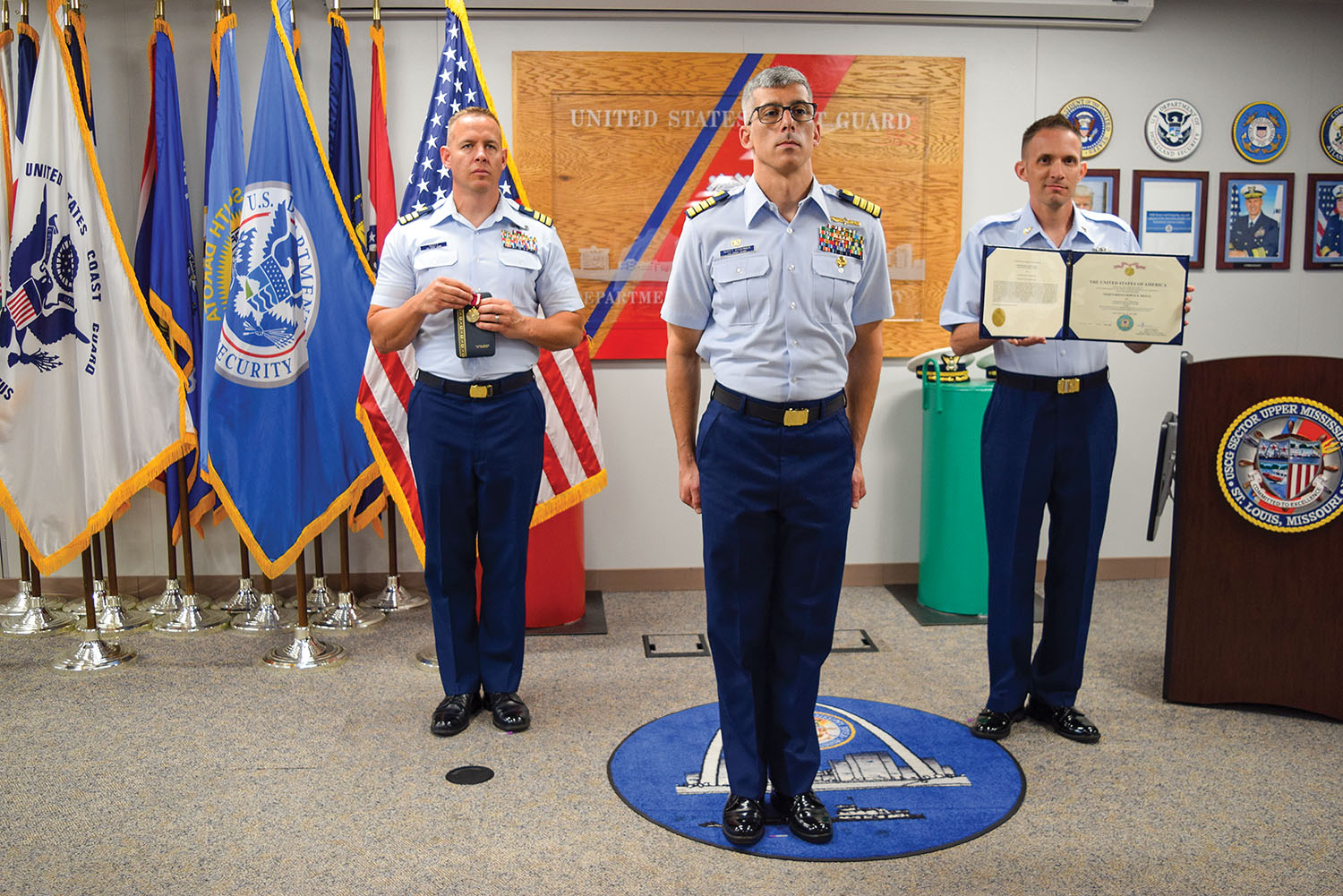 From left, Cmdr. Richard M. Scott, Capt. Scott A. Stoermer and Senior Chief Petty Officer Scott A. Manfre, command senior chief, Sector Upper Mississippi, are shown at the sector's May 27 change of command ceremony, during which Stoermer passed command to Scott. (U.S. Coast Guard photo by Petty Officer 2nd Class Monika Spies)
