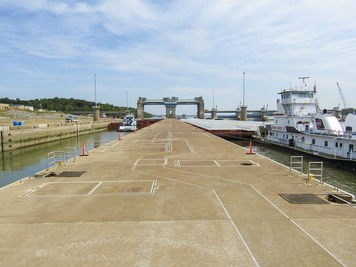 "—Photo courtesy of Louisville Engineer District Two upbound tows lock through at Olmsted Locks and Dam in September 2019. In June, the Corps raised the wickets for the first time in 2020, the fourth time since Olmsted opened in August 2018. By Shelley Byrne River traffic has locked through the twin 1,200-foot-by-110-foot chambers at Olmsted Locks and Dam for the first time this year and only the fourth time in the project's history. ""The weather conditions over the past couple of years have been unique, but raising it in June is much more normal,"" said Ryan Lawrence, assistant operations manager for the Louisville Engineer District's locks and dams project office. Olmsted personnel began raising the wicket dam June 18. It had also been raised in August 2018, August 2019 and November 2019, for a total of about 100 days, Lawrence said. The longest period was in August 2019, when the wicket dam held pool for 62 days at 301.5 feet above sea level, maintaining the pool 46 river miles, back to the Smithland Locks and Dam. A more typical elevation at Olmsted is 295 to 300 feet, based on a hinged pool that takes advantage of the natural slope of the river. Crews began lowering the wickets June 23 in response to rainfall in the upper Ohio Valley, but Lawrence said they may need to go back up again in another two weeks or so, given current forecasting that calls for less rain and a falling Mississippi River. The Corps said it expects to raise and lower the wickets an average of four times each season. ""But so far we haven't really had an average year,"" Lawrence said. ""You do what needs to be done to maintain the river elevations."" Given the weather so far this year, the Corps believes this season may be much closer to a typical one than the last two have been. However, Lawrence cautioned, ""As we saw last year, there's no real way to know. We look at historical trends and what we expect with weather patterns."" Although the Corps had plenty of experience with wickets at the former Locks and Dams 52 and 53, Olmsted modernized the process when it opened in August 2018 on the Ohio River near Olmsted, Ill. In addition, instead of a hook blindly grabbing for a bar on the wickets beneath the water, GPS and a sonar camera aid the process. ""They really took the things they learned from 52 and 53 and implemented and improved those things here,"" Lawrence said. The Corps has less experience using tainter gates combined with a wicket dam to control flow. Olmsted has five tainter gates, while the former projects didn't have any, although other Ohio River locks and dams in the district have them. The gates can be opened and closed to maintain the pool without raising and lowering the wickets as frequently. ""We're definitely still learning that,"" Lawrence said, adding that Olmsted has a unique combination of factors since high water on the Mississippi River can back up the Ohio to as far as Olmsted and since levels on Kentucky Lake on the Tennessee River, Lake Barkley on the Cumberland River and on the Ohio at Smithland"