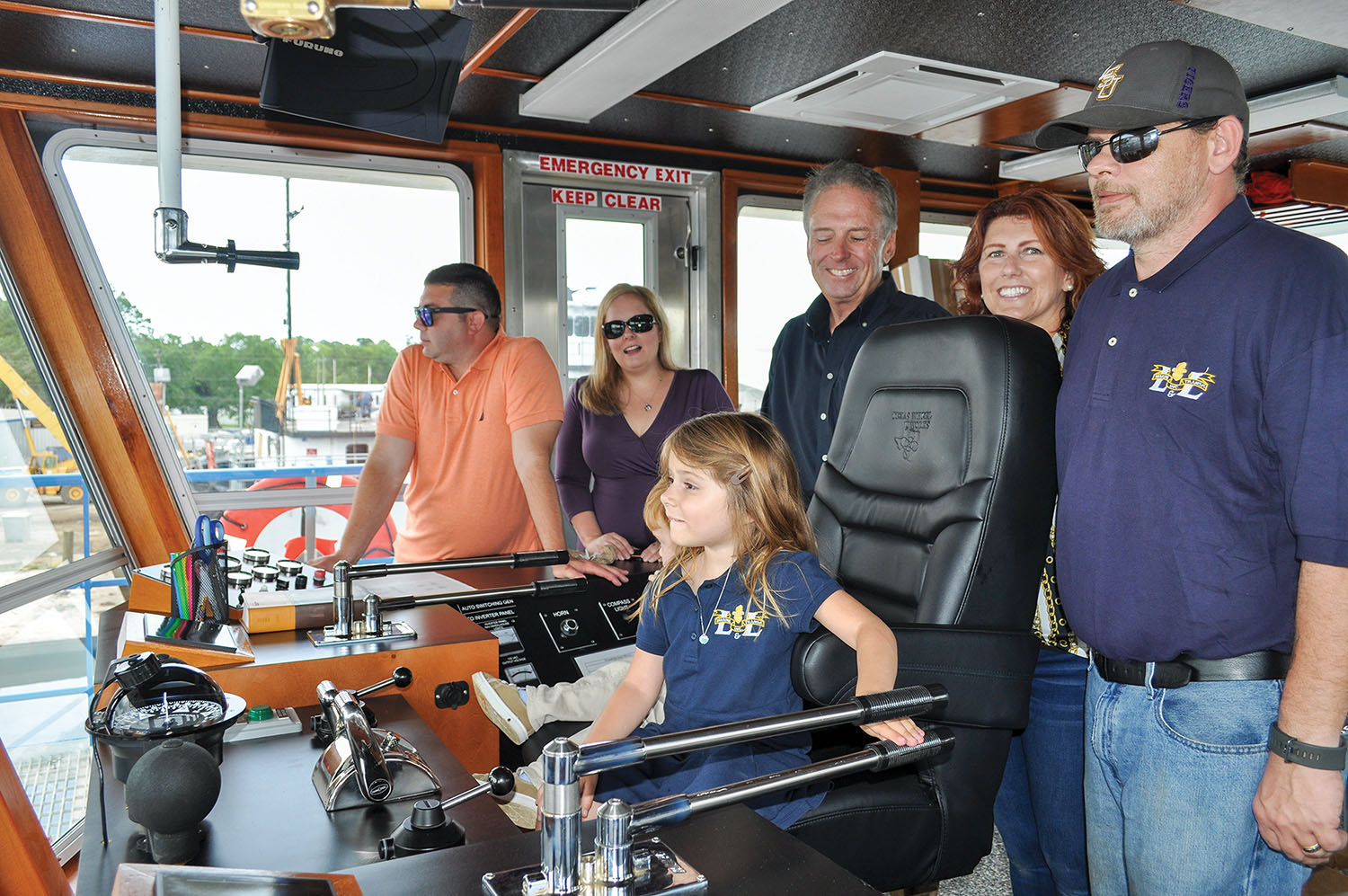 Amelia Ray Balser seated in pilot chair, surrounded by, from left: Ray and Melissa Balser, Lee and Angela LeBoeuf and Capt. Miles Shank. (Photo courtesy of L&L Marine)