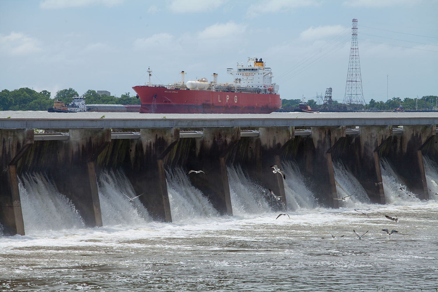 A tanker on the Mississippi River passes the Bonnet Carré Spillway in May 2019, during one of the spillways two high-water openings that year. (Photo by Frank McCormack)