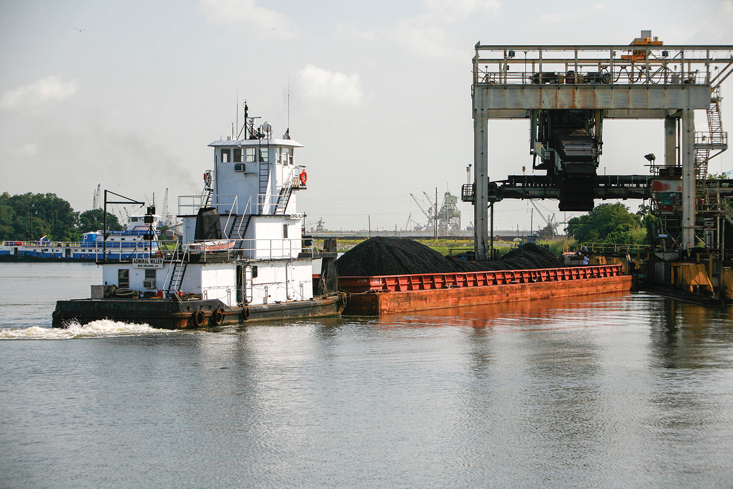 A towing vessel pushes a coal-laden barge into an unloader at the Port of Mobile's McDuffie Coal Terminal. (Photo courtesy of Alabama State Port Authority)