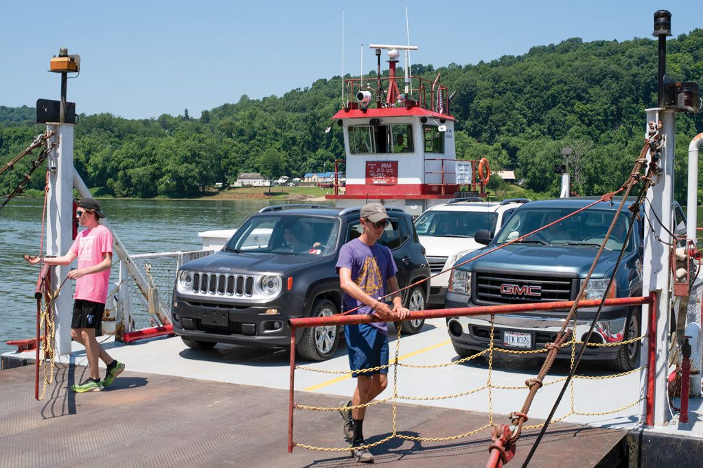 Deckhands James Street, left, and Spencer Corley open the gates to allow traffic off the ferry at Sistersville, W.Va. (Photo by Jim Ross)
