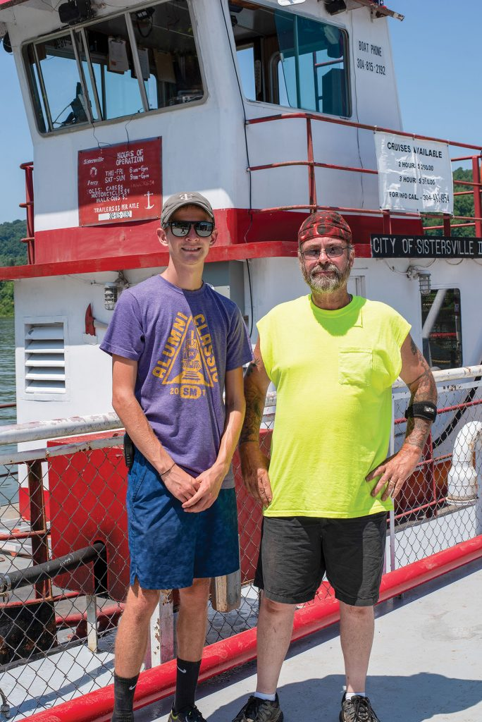 Capt. Bo Hause, right, pilots the Sistersville ferry. He hopes he can have his grandson, Spencer Corley, hired as a deckhand so he can learn how to run the service someday. (Photo by Jim Ross)