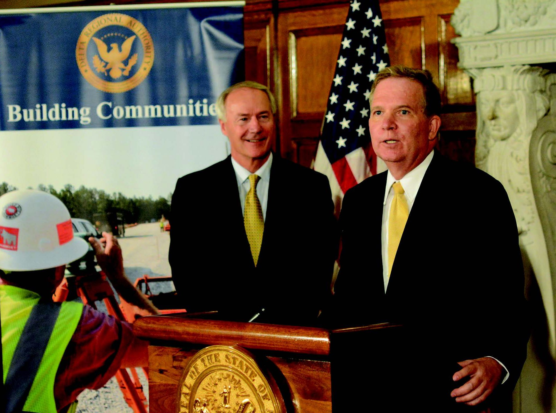 —Helena Harbor Helena Harbor port director John Edwards thanks Gov. Asa Hutchinson in 2017 for helping with a grant to the port as the governor looks on.